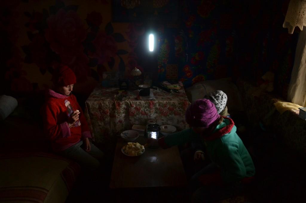 Georgiana, Andreea si Cosmin la lumina lampii, singura lor sursa de lumina